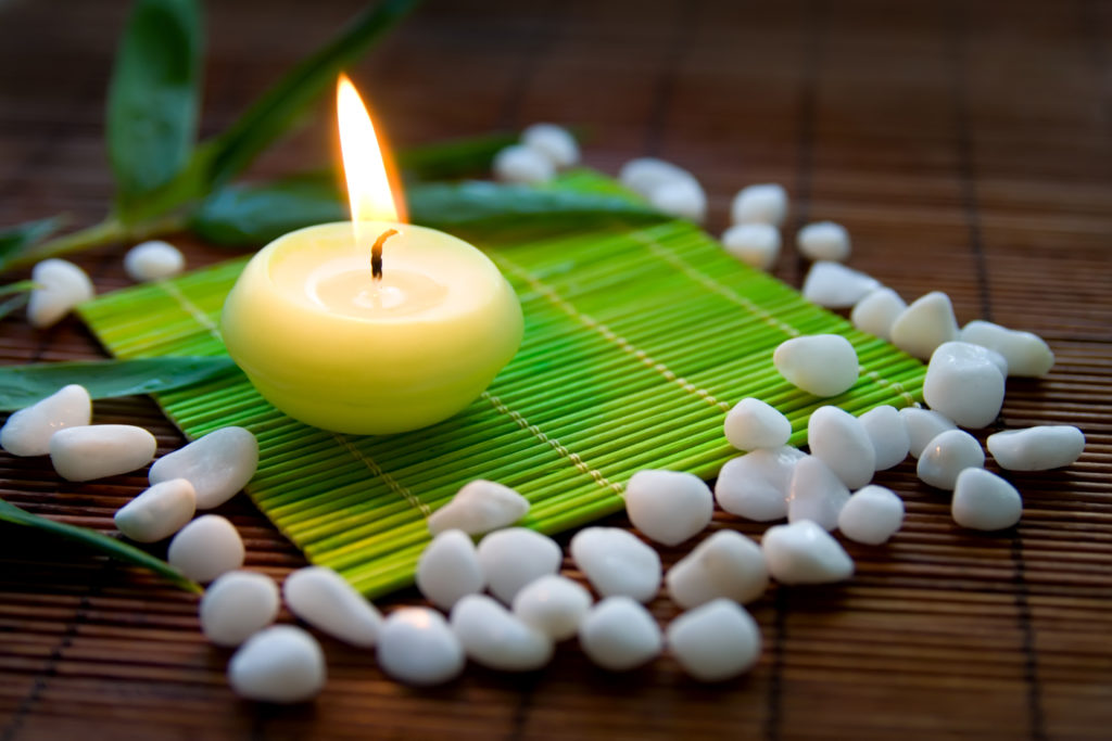 Flaming candle white stones and bamboo leaves - a composition symbolizing meditation and inner harmony